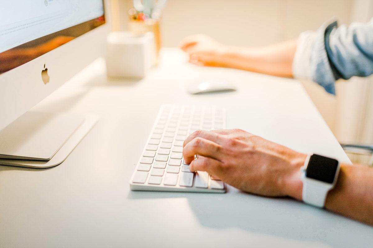 Hände eines Menschen die gerade einen CO2 Rechner an einem Computer bedienen.
