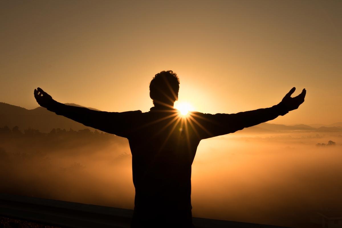 Bild eines Menschen mit ausgebreiteten Armen vor der untergehenden Sonne