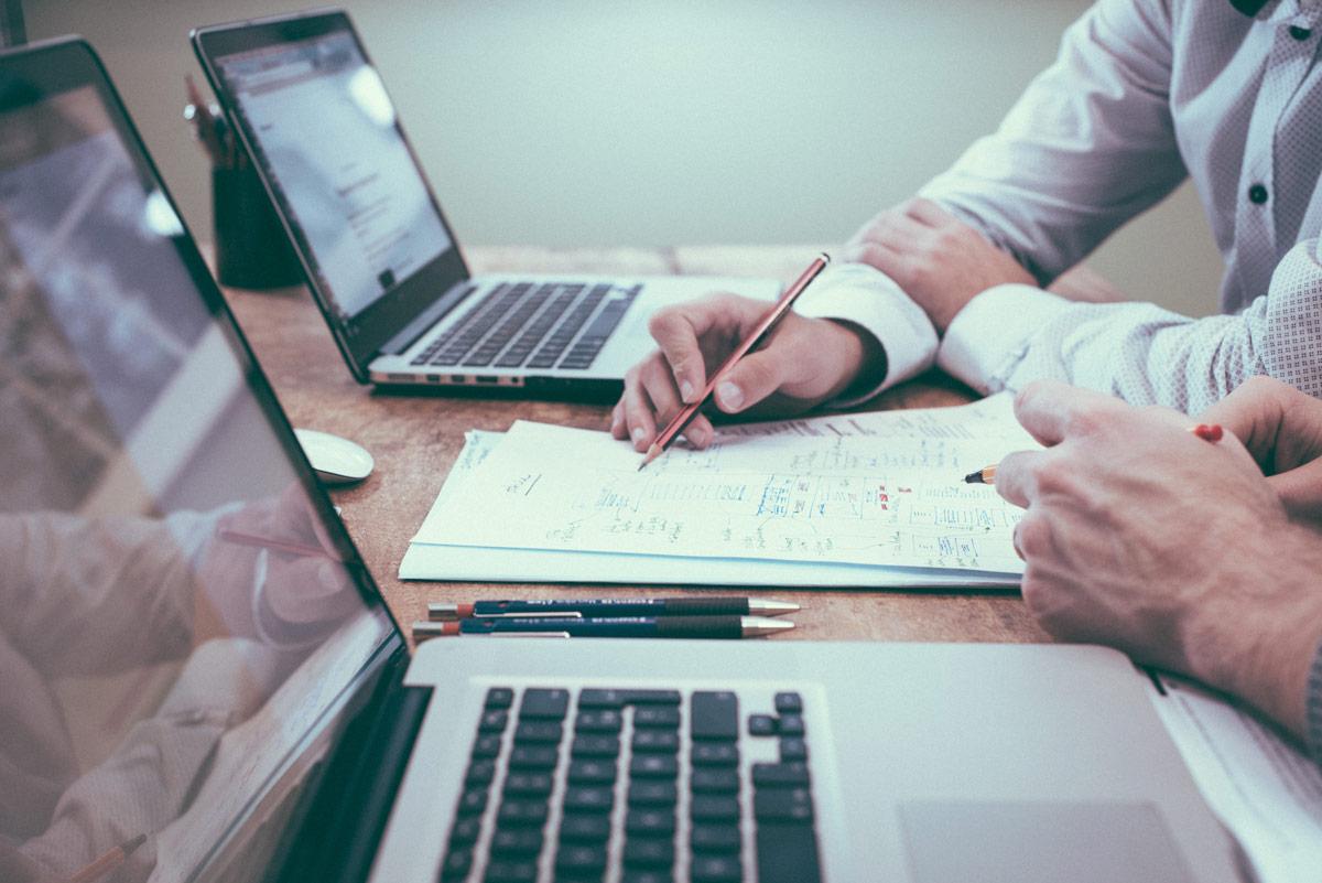 Bild von Laptops, Stiften, Blättern und Menschen die gemeinsam an der Planung von Förderungen arbeiten